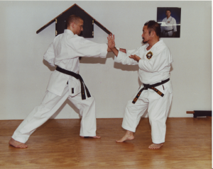 9th Dan, Soke Takayoshi Nagamine demonstrates chudan shuto uke (middle knife hand block) on 4th Dan, Sensei Michael Norvell.