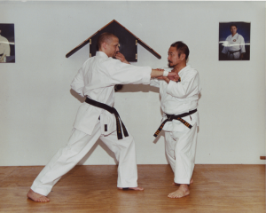 9th Dan, Soke Takayoshi Nagamine demonstrates jodan uchi-shoto-zuki (upper inner knife-hand strike) on 4th Dan, Sensei Michael Norvell.